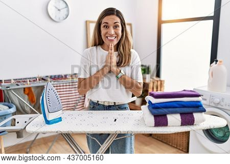 Young hispanic woman ironing clothes at laundry room praying with hands together asking for forgiveness smiling confident.