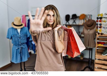 Young blonde woman holding shopping bags at retail shop doing stop gesture with hands palms, angry and frustration expression