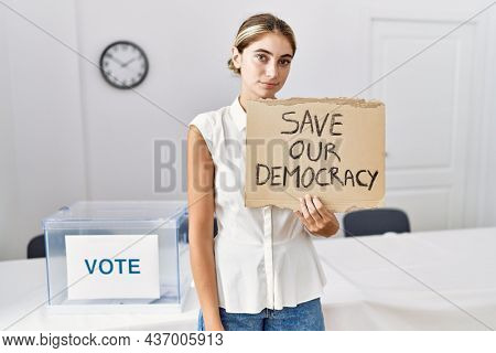 Young blonde woman at political election holding save out democracy banner thinking attitude and sober expression looking self confident