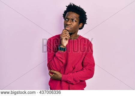 Young african american man wearing casual clothes with hand on chin thinking about question, pensive expression. smiling with thoughtful face. doubt concept.