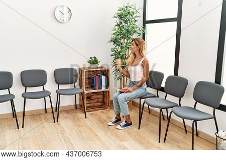 Young caucasian girl smiling happy drinking coffee at waiting room.