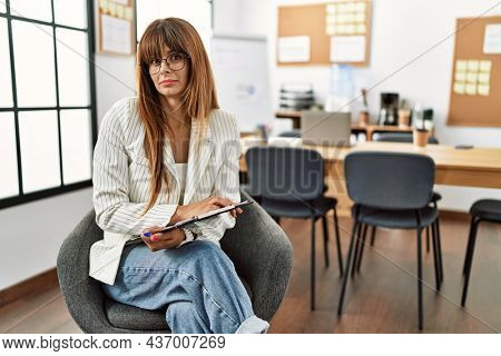 Hispanic business woman working at the office looking sleepy and tired, exhausted for fatigue and hangover, lazy eyes in the morning.