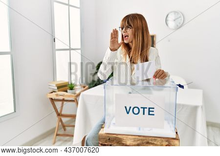 Hispanic business woman voting putting envelop in ballot box shouting and screaming loud to side with hand on mouth. communication concept.