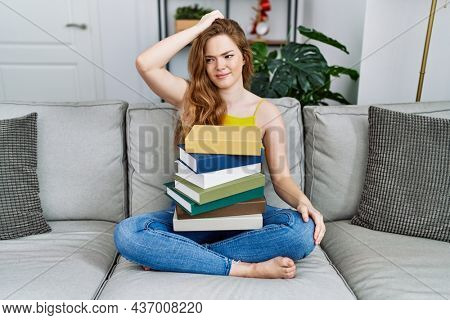 Young caucasian woman sitting on the sofa with books at home confuse and wonder about question. uncertain with doubt, thinking with hand on head. pensive concept.