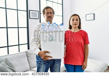 Middle age interracial couple holding recycling bin with plastic bottles at home thinking attitude and sober expression looking self confident