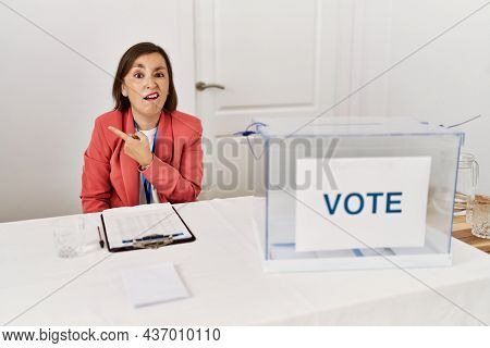 Beautiful middle age hispanic woman at political election sitting by ballot pointing aside worried and nervous with forefinger, concerned and surprised expression