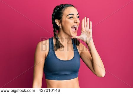 Young brunette girl wearing sportswear and braids shouting and screaming loud to side with hand on mouth. communication concept.