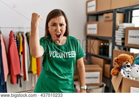 Beautiful middle age hispanic woman wearing volunteer t shirt at donations stand annoyed and frustrated shouting with anger, yelling crazy with anger and hand raised