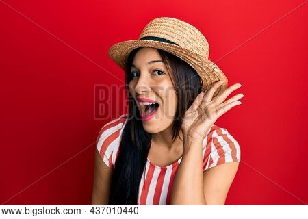 Young latin woman wearing summer hat smiling with hand over ear listening and hearing to rumor or gossip. deafness concept.