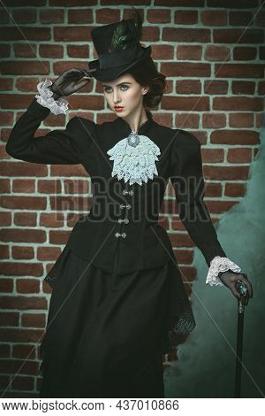 Vintage portrait of a beautiful young brunette lady of the 19th century posing in the background of a brick wall. 19th century hairstyle, makeup and fashion.