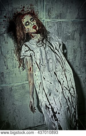 Portrait of a creepy, devil-possessed woman with pale eyes and tousled hair wearing  bloody nightie slides down the blood-covered wall. Zombie woman. Horror, thriller. Halloween.