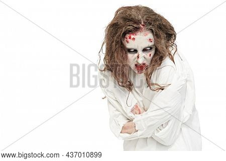 A crazy, devil-possessed woman with pale eyes and disheveled hair, covered in blood, bends in a straitjacket against a white wall. Zombie woman. Horror, thriller. Halloween. Copy space.