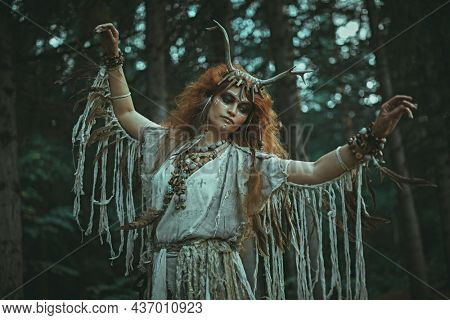 A mystical woman shaman in ethnic dress and deer antlers headdress performs a ritual dance in a forest. Fairy forest witch. Fantasy. Halloween.