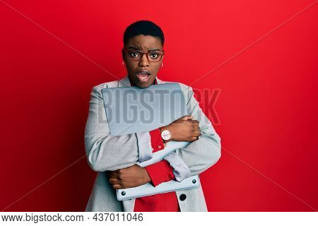 Young african american businesswoman holding laptop in shock face, looking skeptical and sarcastic, surprised with open mouth