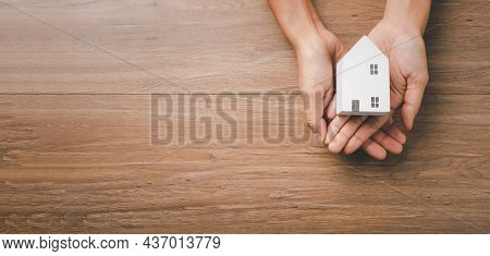Woman Hand Holding Wooden House On Yellow Background, Homeless Housing And Home Protecting Insurance