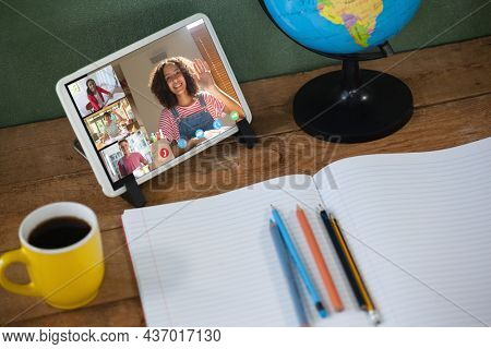 Smiling diverse high school pupils during class on tablet screen. communication technology and online education, digital composite image.