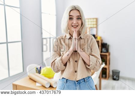 Young beautiful caucasian woman at construction office praying with hands together asking for forgiveness smiling confident.