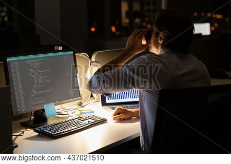 Caucasian male programmer sitting at desk, drinking coffee, using computer with coding on screen. coding, programming and computer technology digital composite image.