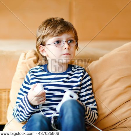 Cute Little Blond Kid Boy With Glasses Playing With A Video Game Console. Child Having Fun At Home D