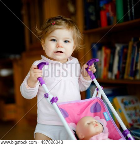 Cute Adorable Baby Girl Making First Steps With Doll Carriage. Beautiful Toddler Child Pushing Strol