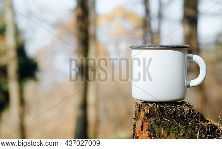 Empty Metal Hiking Mug Mock-up Standing On Tree Stump In Woods Outdoors, Copy Space. Blank New Ename