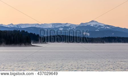 Natural Tranquil Scene Of Sunset With Background Of Blue Snowcapped Mountain Range, Forest Lake And
