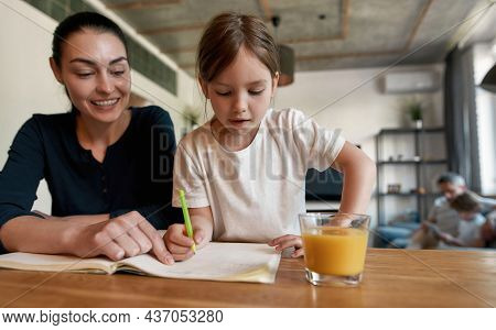 Pensive Small Caucasian Girl Kid Write In Notebook Do Homework With Caring Mom Study At Home. Little