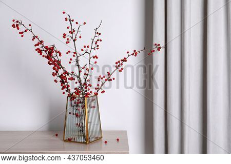 Hawthorn Branches With Red Berries In Vase On Wooden Table Indoors, Space For Text