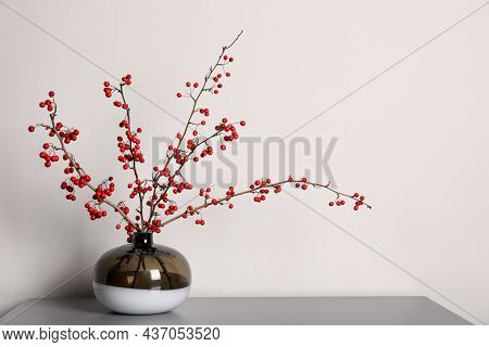Hawthorn Branches With Red Berries In Vase On Grey Table Indoors, Space For Text