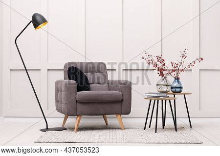 Hawthorn Branches With Red Berries In Vases, Armchair And Lamp Indoors. Interior Design
