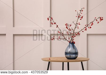 Hawthorn Branches With Red Berries In Vase On Wooden Table Near White Wall Indoors, Space For Text.