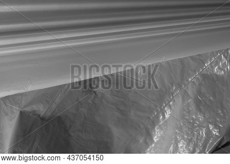 Lines of reflecting light and shadow on pleats and creases in plastic sheeting. monochrome light and texture, abstract background image.
