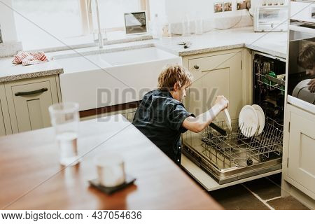 Boy putting dish to dishwasher, household chores for kids