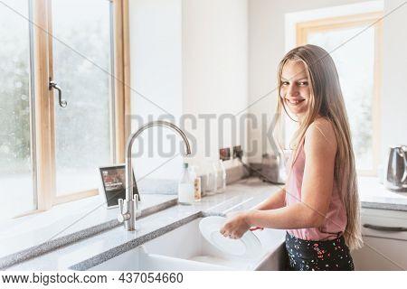 Girl washing dishes, basic house chores