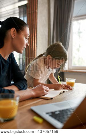 Vertical Narrow Shot Of Loving Young Caucasian Mother Help Small Daughter With Homework Assignment W