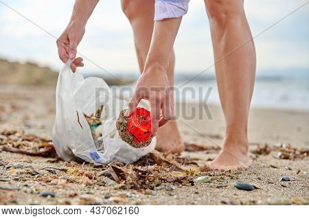 Close-up Of A Womans Hands Picking Up Plastic Trash Into A Bag On The Beach