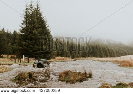 Off-roading car stuck in the water stream in nature