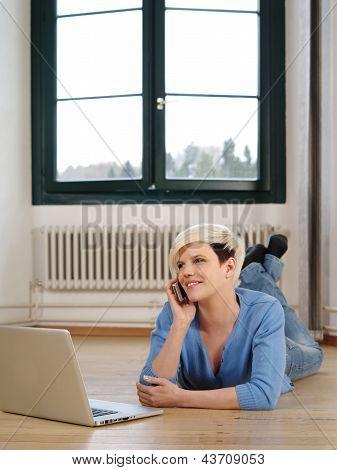 hübsche Frau auf dem Boden mit smartphone