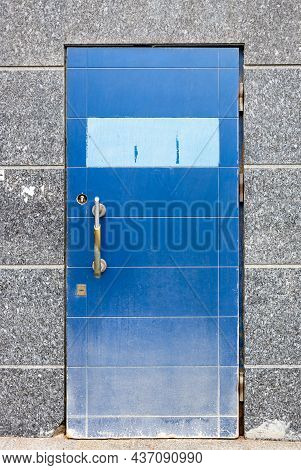 Old Shabby Front Door Covered With Blue Foil In Wall Of City Building Covered With Gray Granite Wall