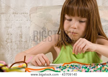 Young girl making bead bracelets