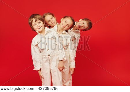 Happy childhood. Cheerful kids in white overalls posing together on a red background. Kid's fashion and style.