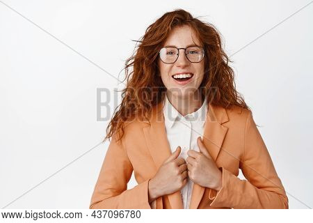Happy Young Female Trainee Dressed As Office Worker, Holding Hands On Her Suit And Smiling At Camera