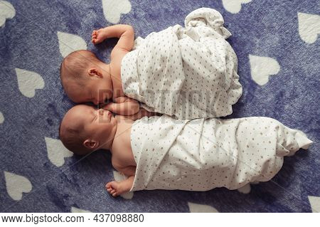 Portrait Of Sleeping Newborn Twins. Twin Girls Wrapped In Diaper With Free Hands. Selective Focus. F