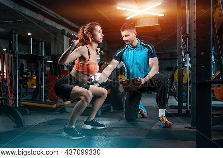 Young Female Workout And Exercising Barbell Squat In Gym With Personal Trainer