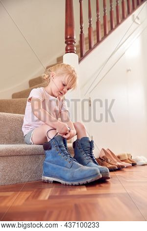 Young Girl Sitting On Stairs Dressing Up And Putting On Father's Work Boots