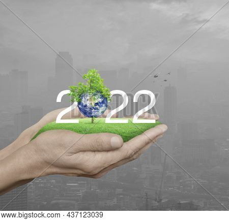 2022 White Text With Planet And Tree On Green Grass Field In Man Hands Over Pollution City Tower And