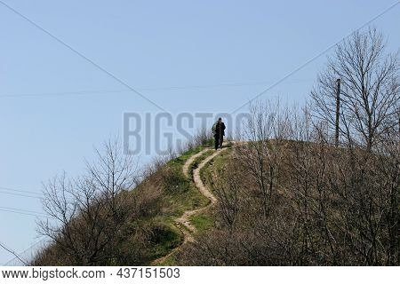 Early Spring, A Man Climbs To The Top Of A Hill Along A Winding Path
