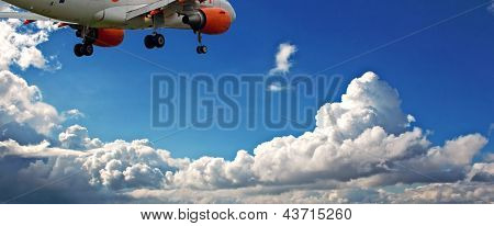 Passenger Jet Against A Blue Sky With White Fluffy Clouds