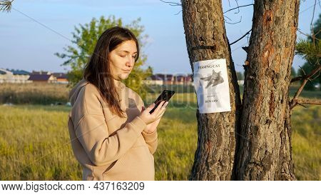 Smiling Woman In Hoodie Dials Number From Missing Cat Poster Hanging On Tree Trunk To Inform Owners
