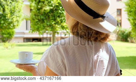 Female In A Straw Hat Holds A Cup Of Hot Drink And Drinks Coffee, Sitting In The Morning On A Summer